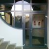 Soluzioni architettoniche con portoncino di ingresso e serramenti fissi di diverse forme e dimensioni